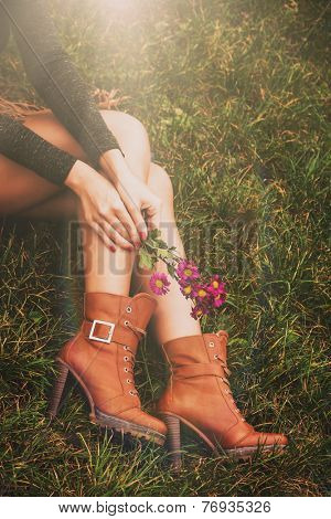 woman legs in brown ankle high heel boots sit on grass hold flowers in hands