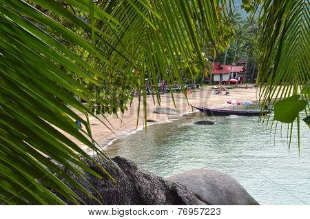 Tropical Paradise - Sandy Beach And Longtail Boat Behing Rocks And Palm Tree Leaves