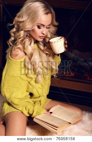 Sexy Woman Reading Book And Drinking Tea Beside A Chimney