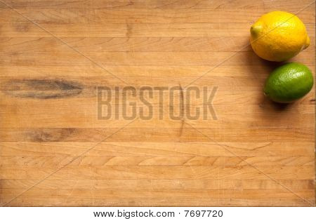 Lime And Lemon On Worn Cutting Board