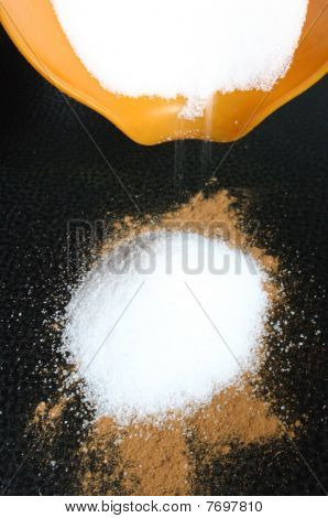 sugar running slowly out of a pot onto a cinnamon pile, as ingredient