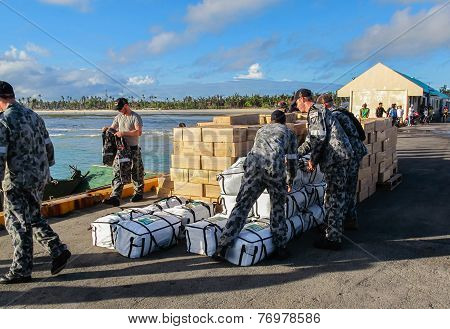 Australian Navy Sailors Unloading International Disaster Relief Supplies From A Landing Craft In The