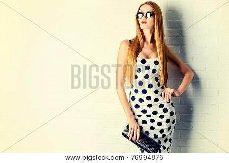 Fashionable lady near white brick wall. Beauty, fashion concept. Optics.