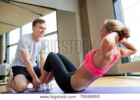 fitness, sport, training, gym and lifestyle concept - woman with personal trainer doing sit ups in gym poster