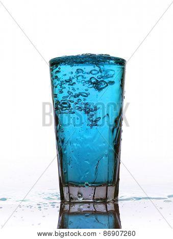Glass of splashing Blue lemonade isolated on white background