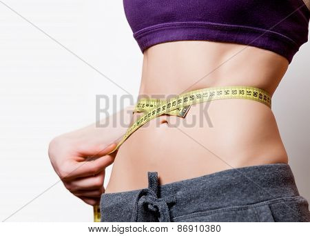 Woman showing her abs with metric after weight loss on white background poster