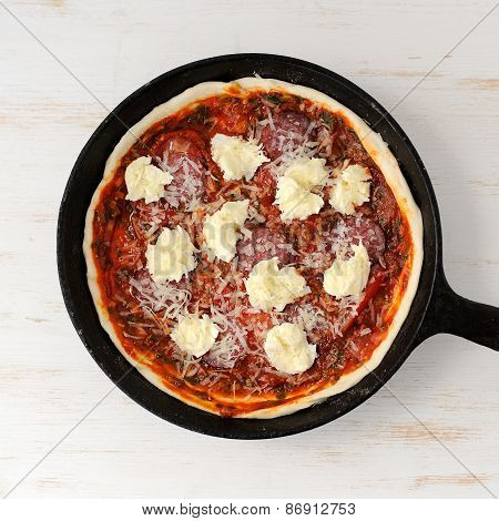 Raw Round Pizza With Salami, Onion, Mozarella In Cast Iron Skillet