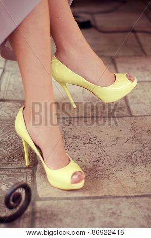 Woman's Legs In Light Yellow Open-toe Pumps. Woman Sitting In A Restaurant.