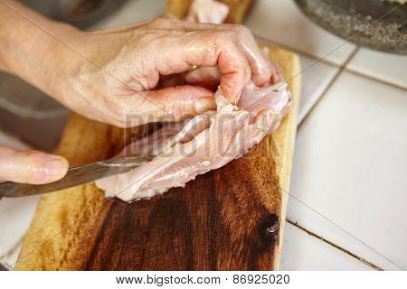 Hand cutting chicken breast on cutting board