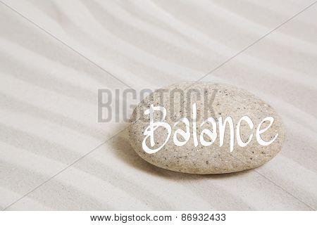Stone in the sand with the word balance. Idea for wellness and recreation concepts.