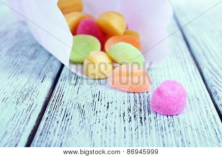 Sweet candies in paper bag on color wooden table, closeup