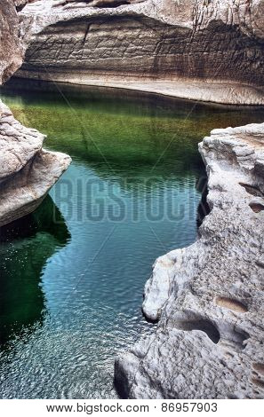 Tranquil rock pool in Wadi Bani Khalid, a well known popular wadi with a perpetual stream near Muscat, Oman