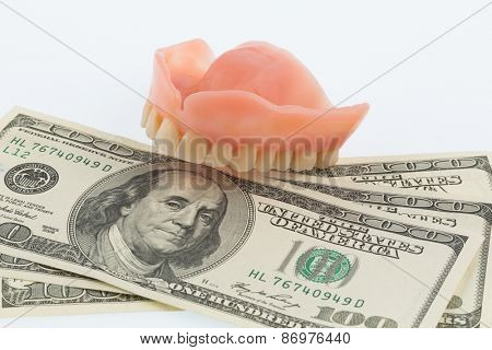 teeth and dollar bills, symbolic photo for dentures, treatment costs and payment