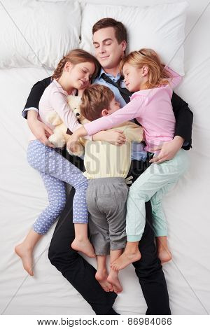 Top view of tired businessman and his three children