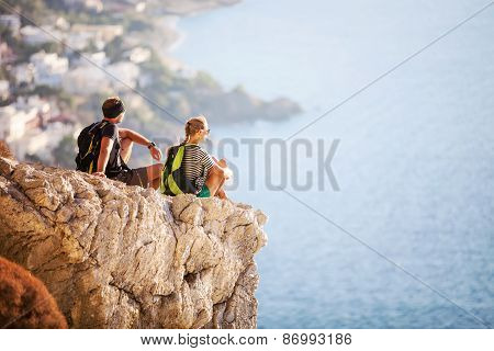 Young couple sitting on rock and enjoying view