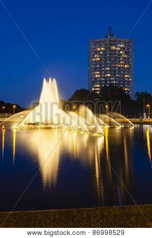 The famous Europaplatz fountain in Aachen Germany at night with a highrise in the background poster