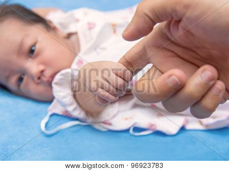 Cute Newborn Baby Hand Holding Mother's Finger