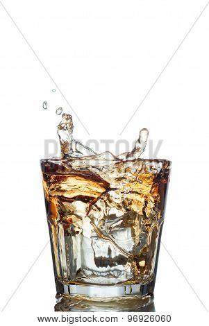 splash of whiskey with ice osolated on white
