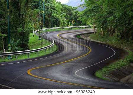 Curve way of asphalt road with yellow line in the green view.