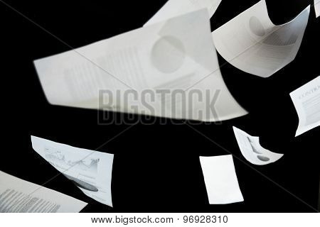 securities, documents, finances and statistics concept - business papers falling down over black background