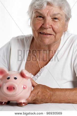 Elder woman holding and hugging funny pink piggybank. Budgeting expenses making savings effective investment concept. Future needs deposit. Focus on pig. Retirement and retiree finansial problems poster
