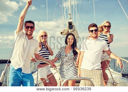 vacation, travel, sea, friendship and people concept - smiling friends sailing on yacht