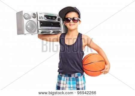 Studio shot of a little boy holding a basketball and a ghetto blaster isolated on white background