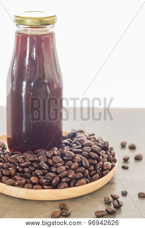 Bottle Of Black Coffee With Roast Bean