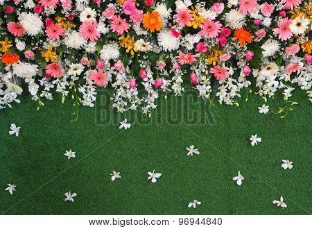 Green backdrop flowers arrangement on turf for wedding ceremony.