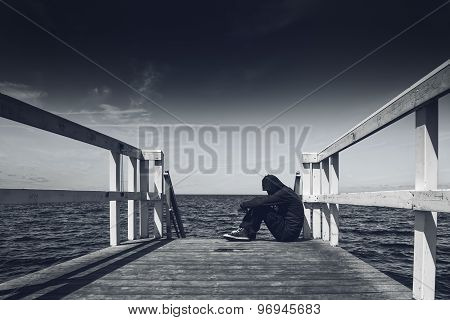 Alone Young Man Sitting at the Edge of Wooden Pier - Hopelessness Solitude Alienation Concept Black and White poster