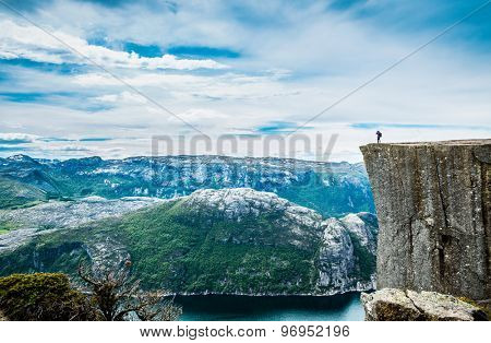 Nature photographer tourist with camera shoots while standing on top of the mountain. Beautiful Nature Norway Preikestolen or Prekestolen. poster