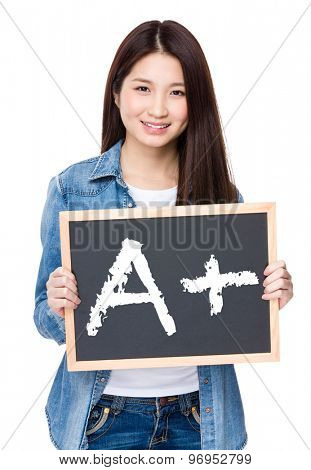 Young woman hold with chalkboard showing A plus mark