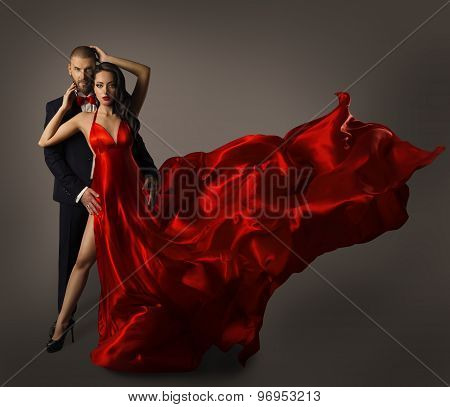 Fashion Couple Portrait Woman Red Dress Man in Suit Long Waving Cloth Flying over Gray Background