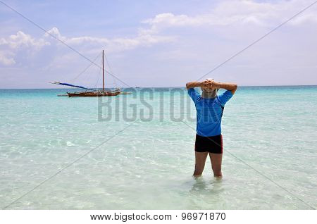 Man is standing in the wather on the beach