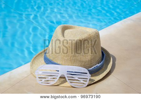 Straw Hat And Party Sunglasses By The Pool
