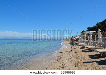 Hiker Practicing Brisk Walk On Long White Sand Beach Near Beautiful Turquoise Transparent Mediterran