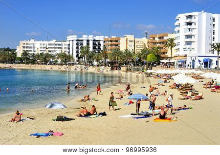 SANTA EULARIA DES RIU, SPAIN - JUNE 14: Sunbathers at Santa Eulalia beach on June 14, 2015, in Santa Eularia des Riu, in Ibiza Island, Spain. Ibiza is a well-known summer tourist destination in Europe