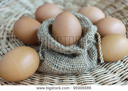 heap of chicken eggs in sackcloth and lay on basketwork easter eggs poster