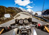 Biker rides a motorcycle on mountain serpentine. First-person view. poster