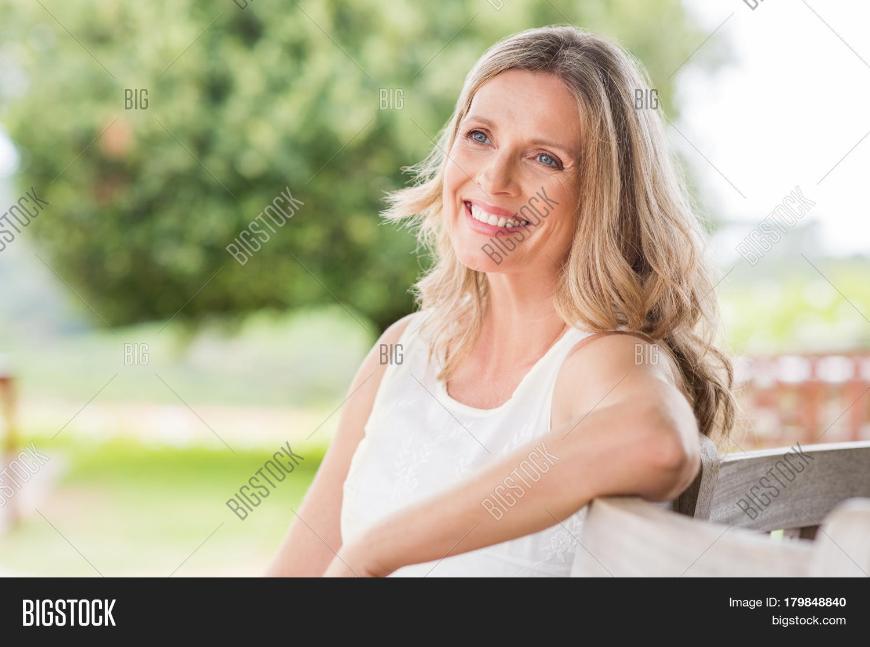 happy blonde mature woman sitting image & photo | bigstock