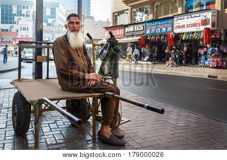 Dubai, UAE - January 9, 2017. Street porter with a cart waiting for work. Unidentified person an elderly man with a gray beard sits on a freight trolley awaiting work in the Deira district, where there are a large number of markets and shops in Dubai