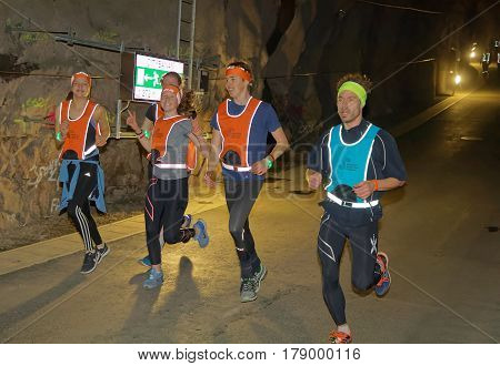 STOCKHOLM SWEDEN - MAR 25 2017: Happy teenagers in reflex vest running in a dark tunnel in the Stockholm Tunnel Run Citybanan 2017. March 25 2017 in Stockholm Sweden