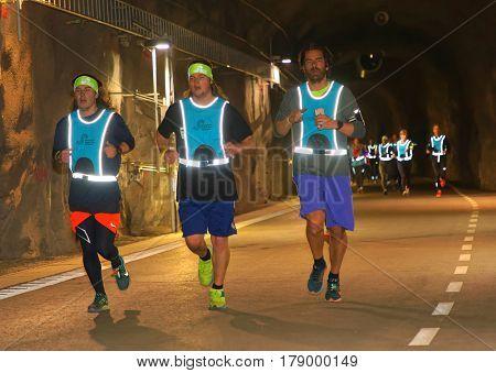 STOCKHOLM SWEDEN - MAR 25 2017: Men in reflex vest running in a dark tunnel in the Stockholm Tunnel Run Citybanan 2017. March 25 2017 in Stockholm Sweden