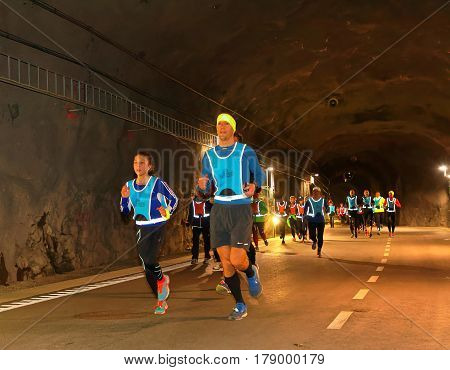 STOCKHOLM SWEDEN - MAR 25 2017: Group of runners in reflex vest in a dark tunnel in the Stockholm Tunnel Run Citybanan 2017. March 25 2017 in Stockholm Sweden