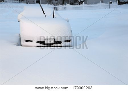 single car covered by snow in blizzard