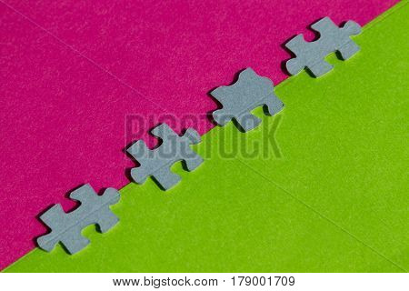Jigsaw Puzzle pieces on border between pink and green background with copy space