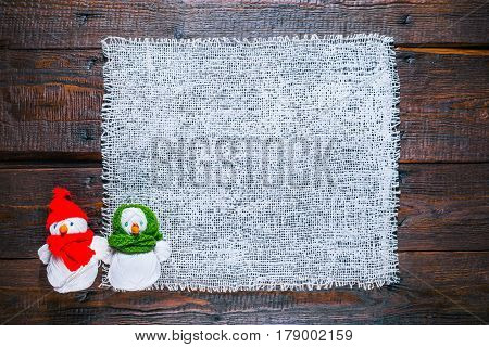 Knit shop background with burlap and couple of handmade snowmen of yarn skeins