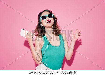 Summer lady. Beautiful asian girl with professional makeup and stylish hairstyle singing and dancing while listening to music on pink background.