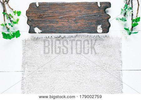 Background of wood planks painted in white and burlap. Bunches of blooming apple tree and young black current twigs in upper corners. Wood signboard
