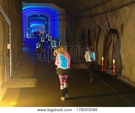 STOCKHOLM SWEDEN - MAR 25 2017: Rear view of people walking in a steep ascent in blue lit tunnel in the Stockholm Tunnel Run Citybanan 2017. March 25 2017 in Stockholm Sweden